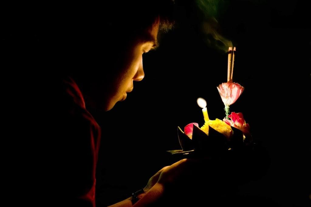 Loy Krathong - Jeune homme priant à la lumière de son Krathong