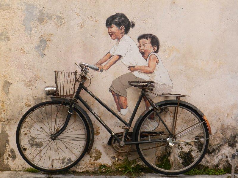 Comment aller à Penang en Malaisie - street art 2 enfants peints sur un vélo posé contre le mur